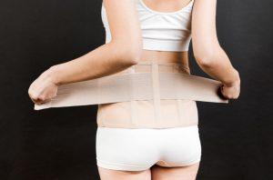 A cinta pós-cirúrgica na abdominoplastia é um cuidado importante que as pacientes precisam tomar logo após realizar essa cirurgia na barriga. O papel da cinta é ajudar na recuperação, por outro lado, não usá-la adequadamente pode envolver certos riscos. Saiba mais aqui. Usar a cinta pós-cirúrgica na abdominoplastia é imprescindível Um pós-cirúrgico bem cumprido é um dos primeiros passos para que a abdominoplastia seja bem-sucedida. Afinal, quando a paciente faz uma cirurgia para diminuir a circunferência abdominal e deixar a região mais reta e com a pele firme, ela quer ver esses resultados assim que possível. Entre os cuidados que devem ser tomados após realizar uma cirurgia de abdominoplastia e miniabdominoplastia está o repouso e o uso de uma cinta ou faixa abdominal pós-cirúrgica ininterruptamente, retirando apenas para o banho. As cintas mais conhecidas de tecido elástico compressivo são de lycra ou cetinete. Há diversos tipos de acessório, inclusive a cinta abdominal que só pega na cintura, ou camisete, body, bermuda e as placas de contenção. Quais são as principais funções da cinta pós-abdominoplastia? O uso desse acessório será imprescindível para atingir os resultados desejados pela paciente, porque garante uma sustentação dos músculos do abdômen e do seu entorno. Além disso, o acessório também modela a região. A cinta pós-cirúrgica abdominoplastia vai proteger a área operada e promover uma pressão no local da cirurgia, permitindo uma fixação da pele, facilitando a cicatrização das incisões, dando segurança e postura à paciente que está se recuperando. Com o uso da cinta, a paciente vai conseguir ficar com a coluna ereta, evitando que a barriga fique projetada para frente e também forme uma corcunda. Entre outras vantagens do uso do acessório está também conter a dor e os edemas (inchaços), que são muito comuns no pós-operatório. Além disso, o uso da cinta para abdominoplastia também vai combater a flacidez. No entanto, esse acessório tem algumas regras de 